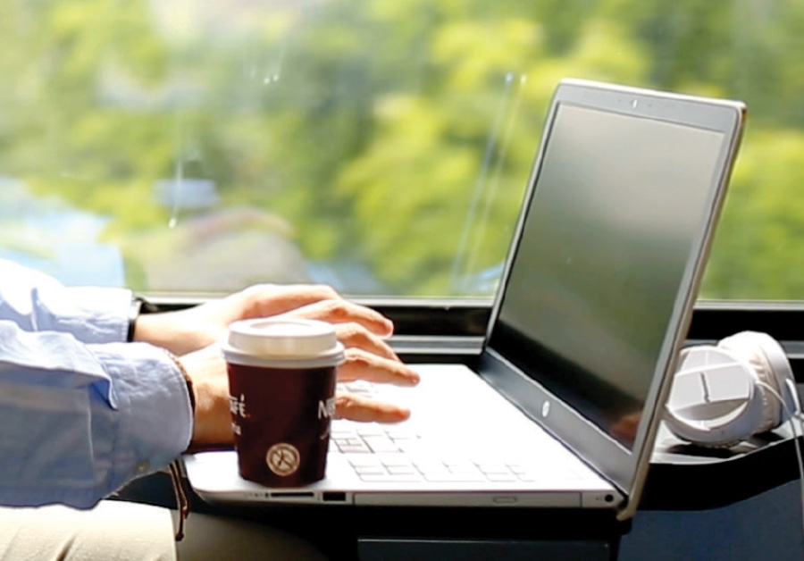 Man working on his computer with a cup of coffee