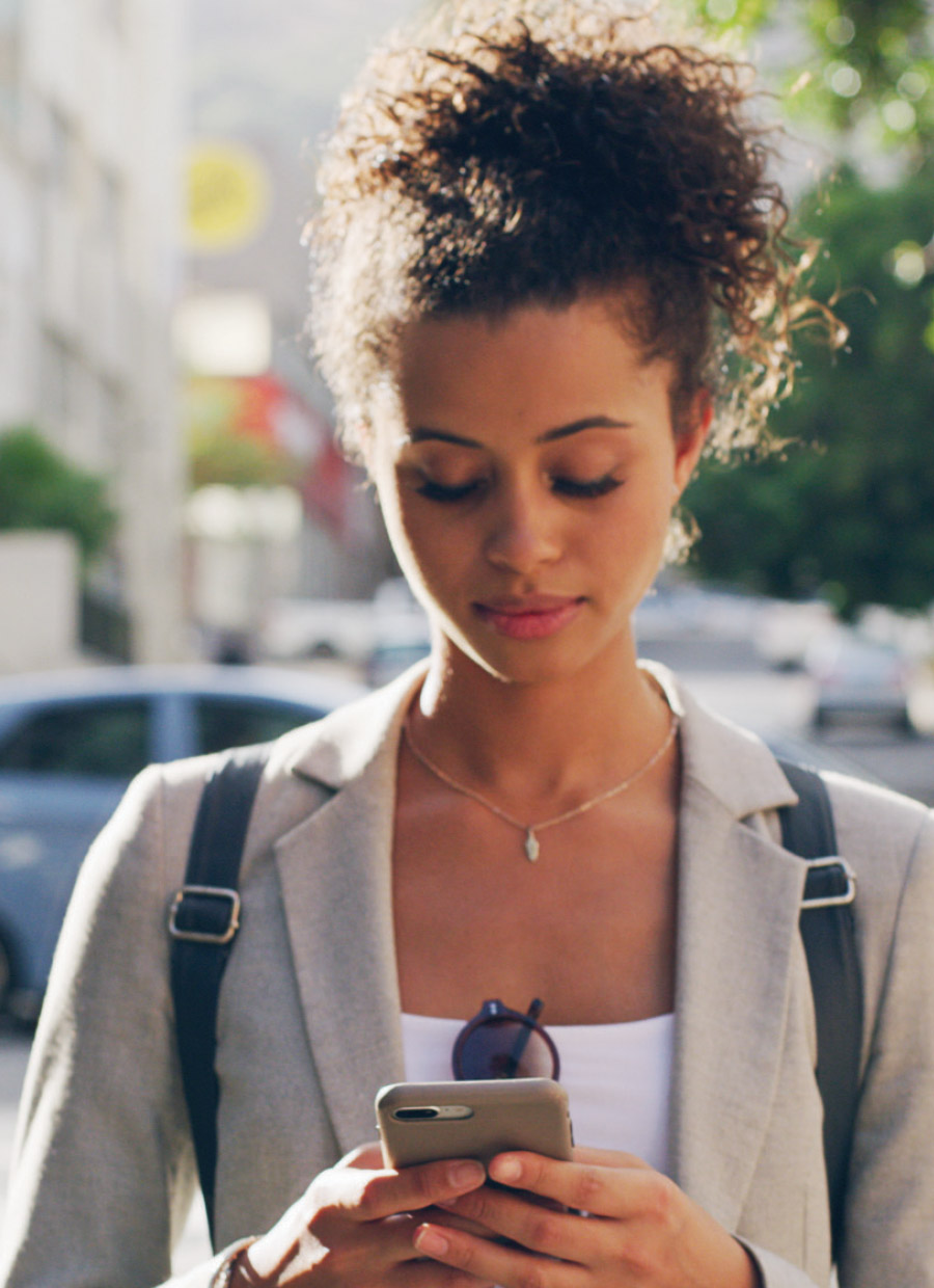 Woman on her phone as she walks through the city