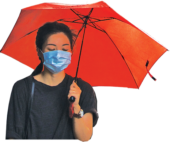 Woman in a mask holding an umbrella