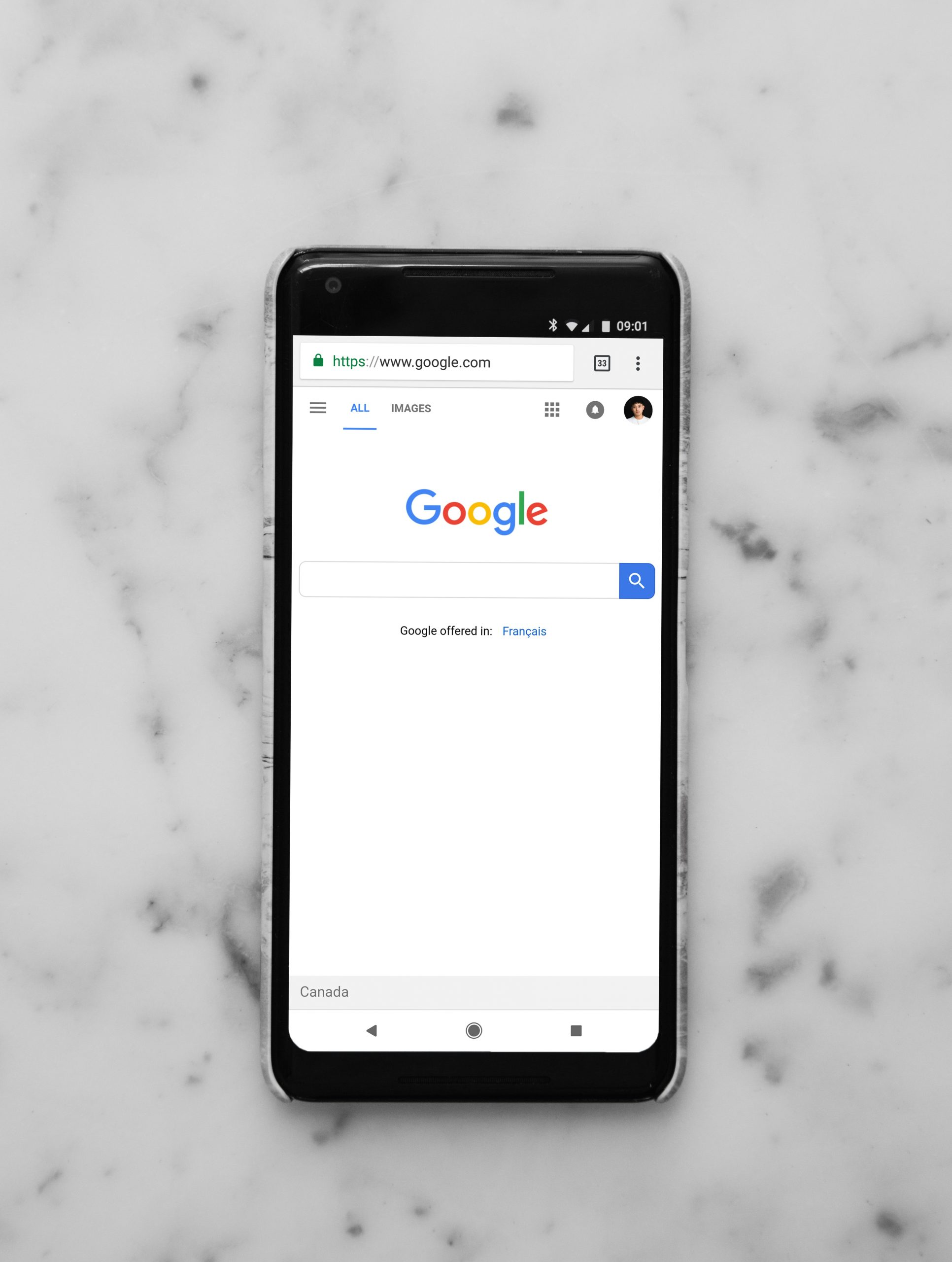 black Android smartphone showing google site on white surface